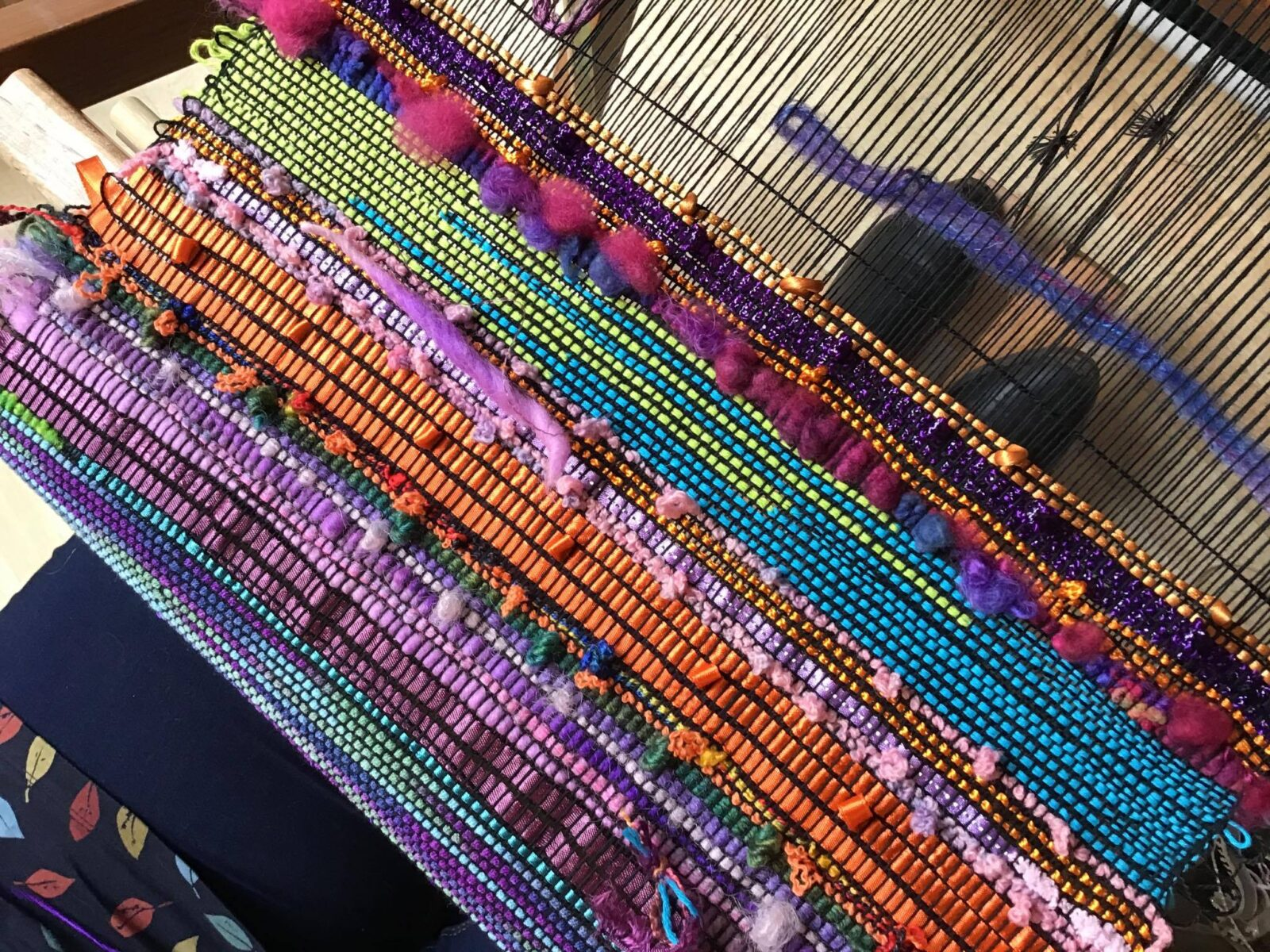 Striped multicoloured textured SAORI weaving on a loom