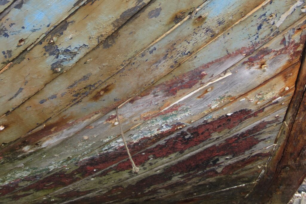 Peeling paint on worn wooden hull of boat