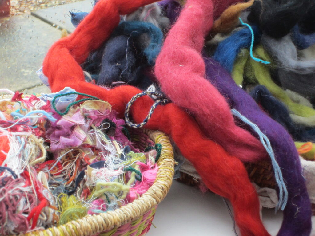 Basket of multi-coloured threads next to a pile of unspun colourful skeins