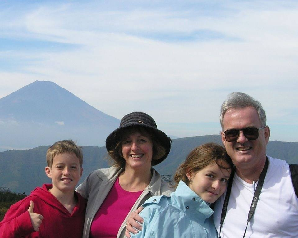 family of four standing in front of mount Fuji