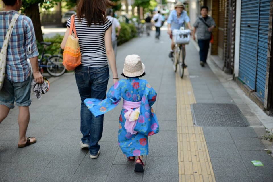 Child dressed in summer kimono walking down the street