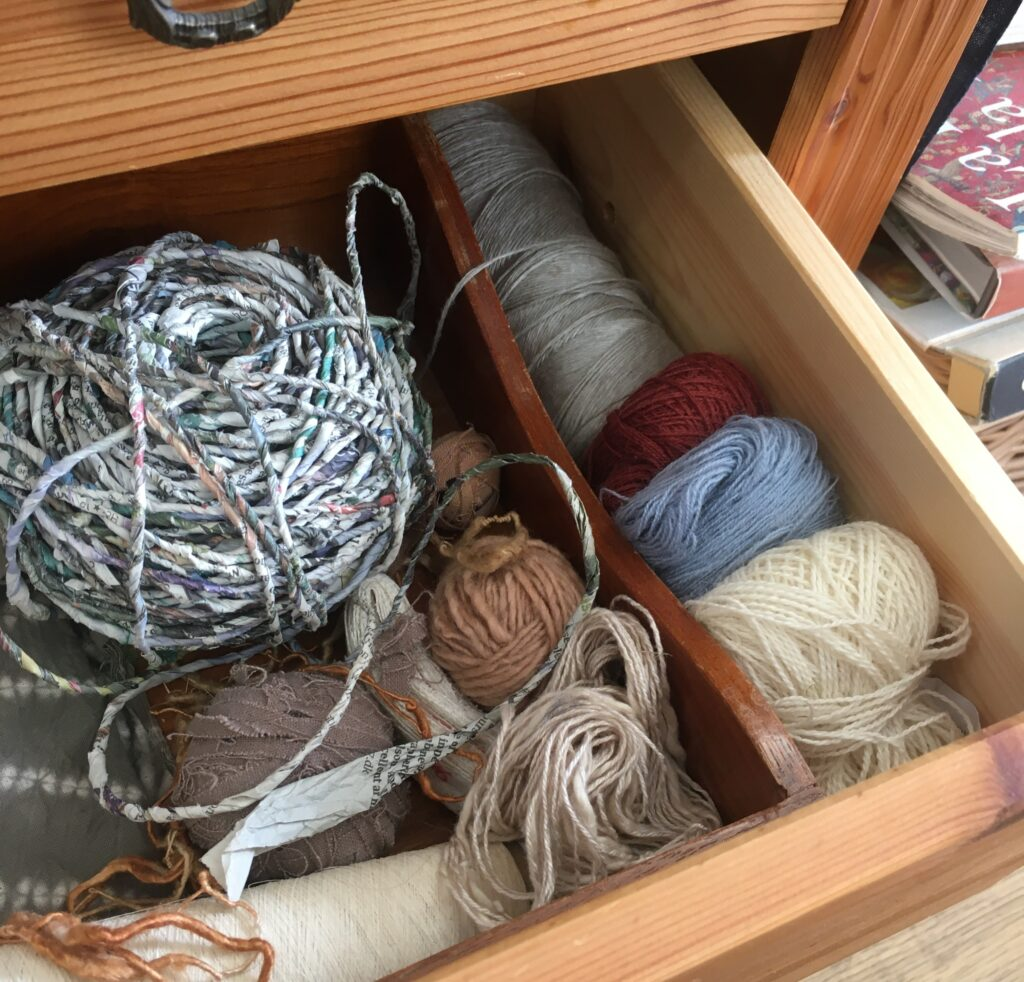 A wooden drawer of different yarns