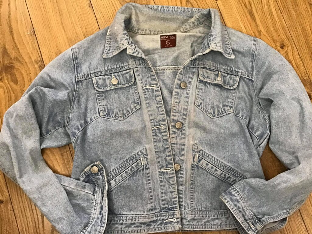 Light blue denim jacket on wooden floor