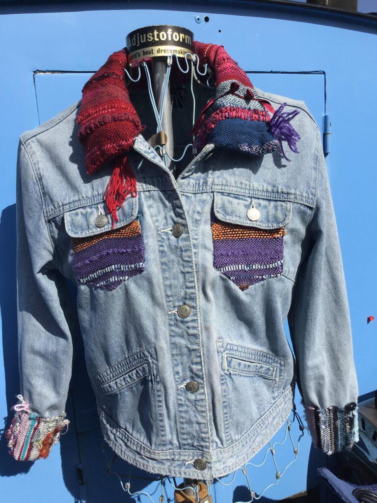 Denim jacket with handwoven details in front of light blue door