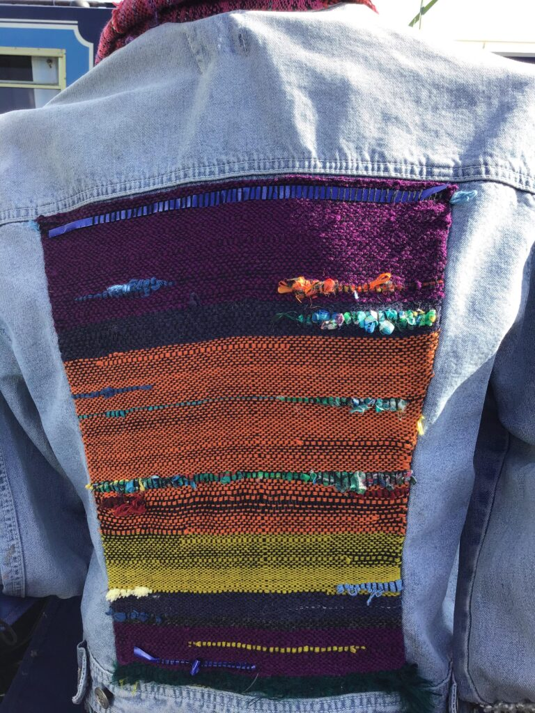 Purple, orange and yellow woven panel at the back of a denim jacket