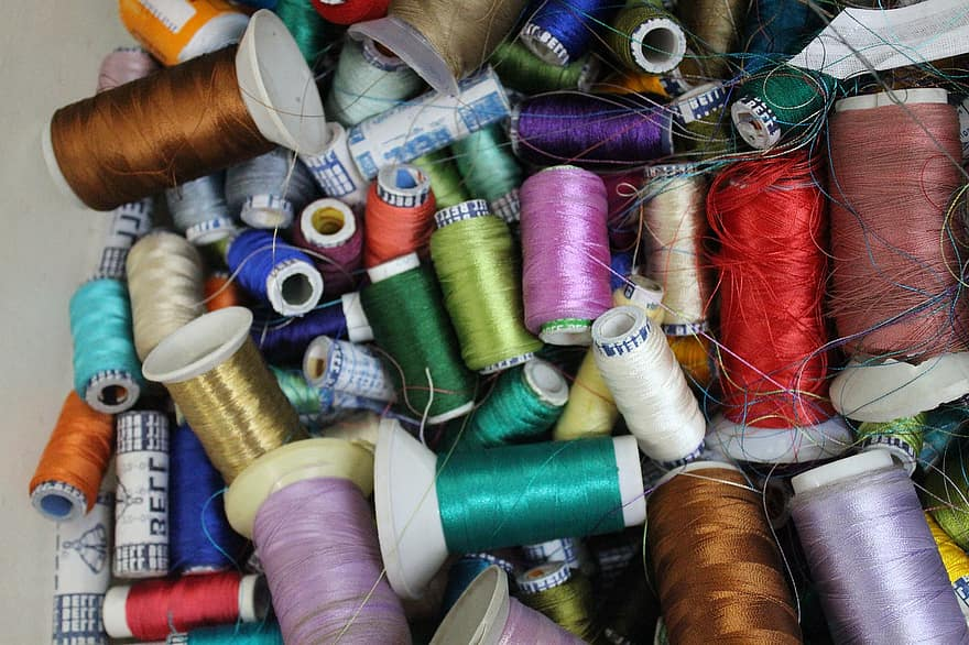 A jumble of differently coloured silk threads on spools